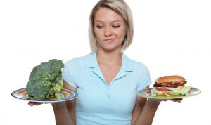 a plate of fresh broccoli on one hand and a cheeseburger on the other