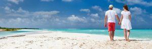 a couple walking on a beach in cuba